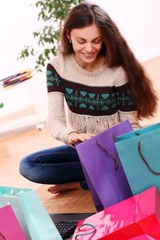 Donna che sorride con i sacchetti della spesa variopinti