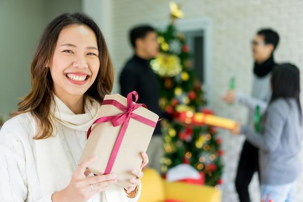 Donna che sorride con il contenitore di regalo della tenuta in salone con il gruppo di amici per natale