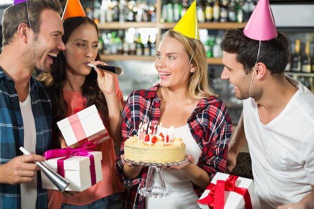 Donna che sorride con la torta in mano