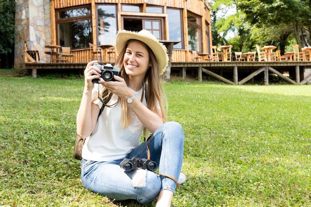 Donna che sorride e che esamina macchina fotografica