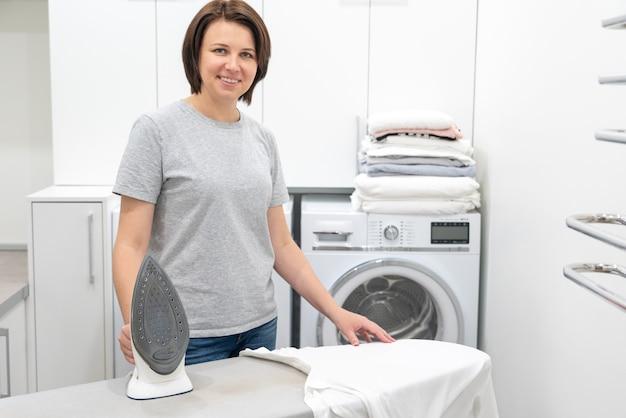 Donna che sorride mentre stando asse da stiro vicino nella stanza di lavanderia con la lavatrice