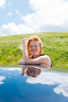 Donna che sorride mettendo le mani sul tetto dalla finestra di automobile