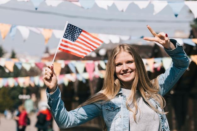 Donna che sorride tenendo la bandiera americana e gesticolando due dita