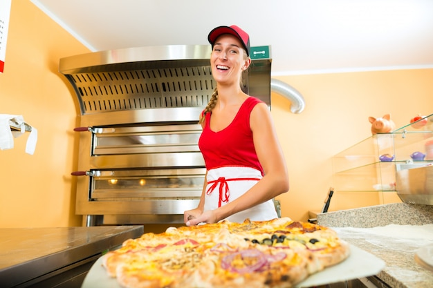 Donna che spinge la pizza finita dal forno