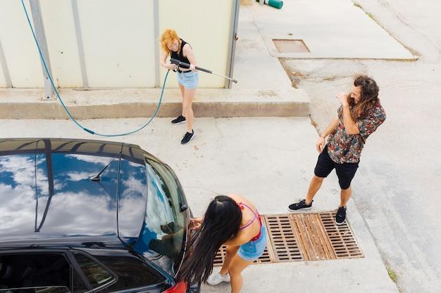 Donna che spruzza acqua sugli amici all'autolavaggio