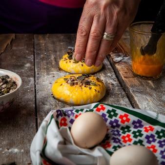 Donna che spruzza le spezie con le mani sulla vista laterale della pasta.