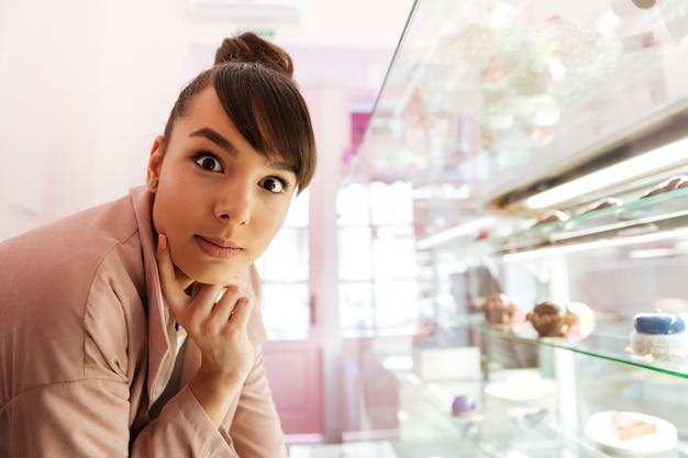 Donna che sta alla vetrina di vetro con patries dentro il caffè