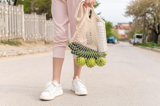 Donna che sta e che tiene borsa riutilizzabile