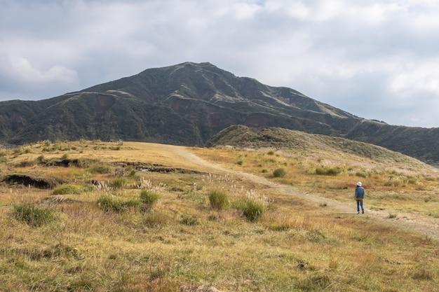 Donna che sta nel lanscape verde con la montagna aso, kusasenri, kumamoto, kyushu