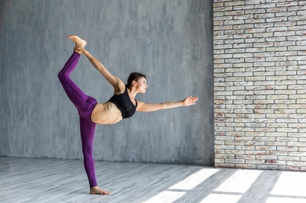 Donna che sta nel signore della posa di yoga di ballo