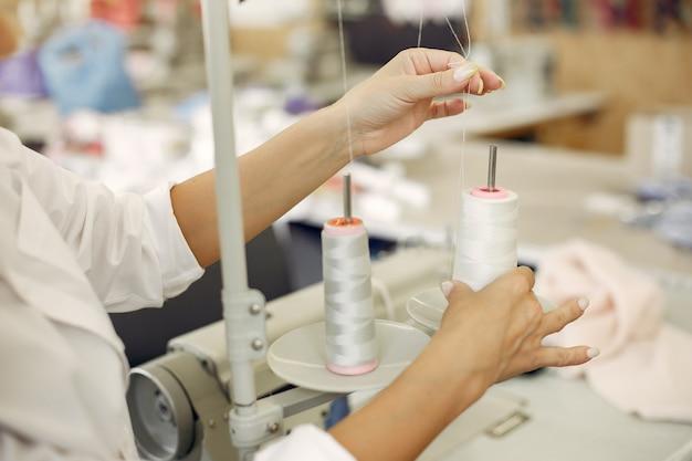 Donna che sta nella fabbrica con un filo