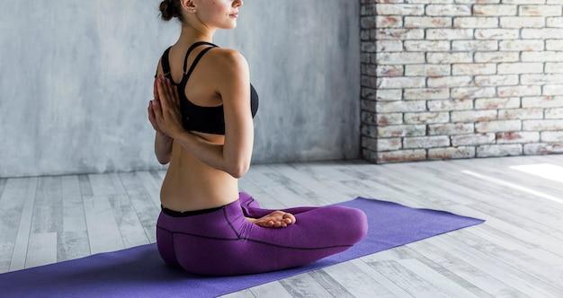 Donna che sta nella posa di yoga del loto con le mani dietro lei indietro