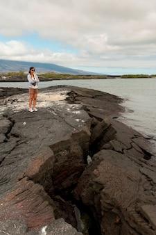 Donna che sta sulla roccia vulcanica sulla costa, punta espinoza, isola di fernandina, isole galapagos, ecuador