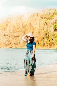 Donna che sta sulla spiaggia sabbiosa dall'oceano
