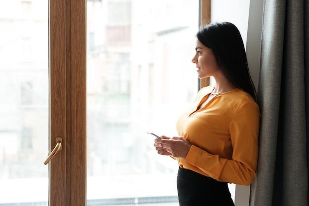 Donna che sta vicino alla finestra con il telefono e distogliere lo sguardo