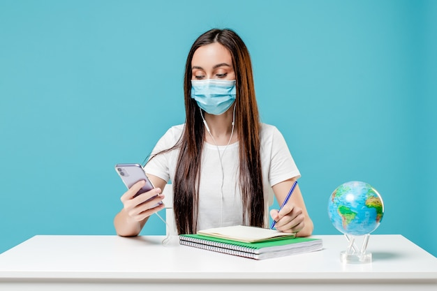 Donna che studia con il globo e il telefono del pianeta terra con i libri che indossano maschera