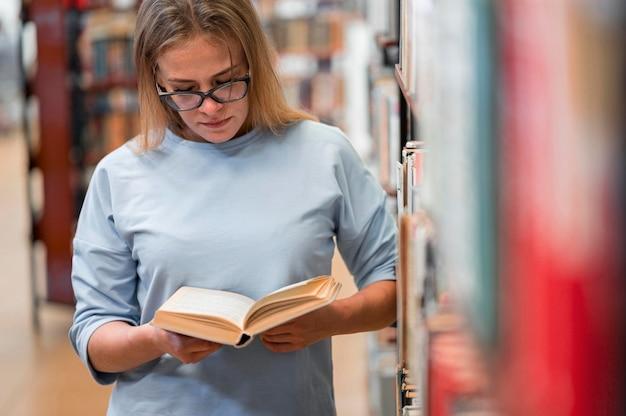 Donna che studia in biblioteca vista frontale