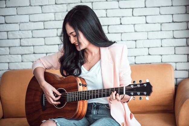 Donna che suona la chitarra sul divano