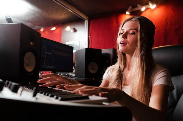 Donna che suona la tastiera e sentire la musica