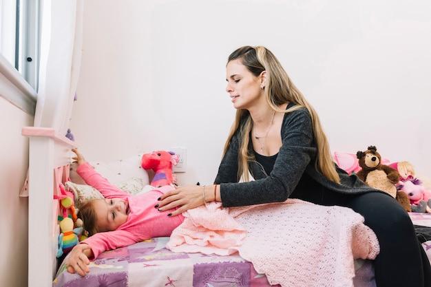 Donna che sveglia sua figlia a letto al mattino
