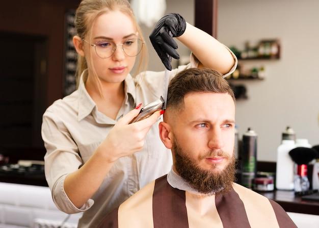Donna che taglia i capelli del suo cliente