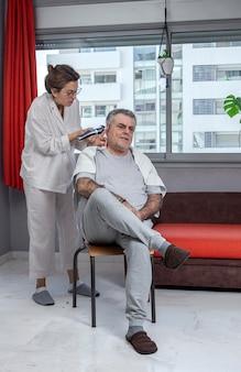 Donna che taglia i capelli di un uomo a casa