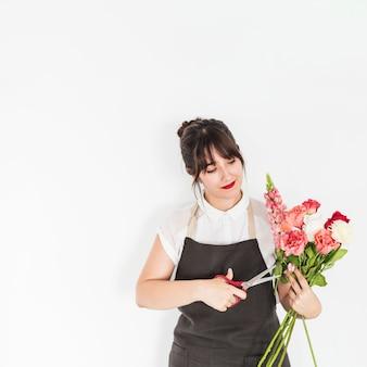 Donna che taglia i ramoscelli dei fiori con le forbici su fondo bianco