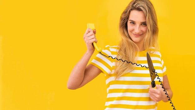 Donna che taglia il filo del telefono