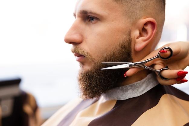 Donna che taglia la barba di un uomo in un negozio di barbiere professionista