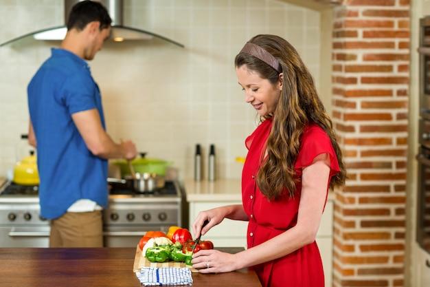Donna che taglia le verdure a pezzi e uomo che cucina sulla stufa in cucina a casa