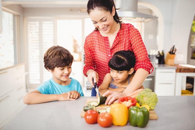 Donna che taglia le verdure a pezzi mentre tabella facente una pausa dei bambini