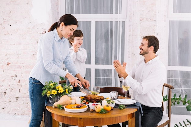 Donna che taglia pollo al forno al tavolo