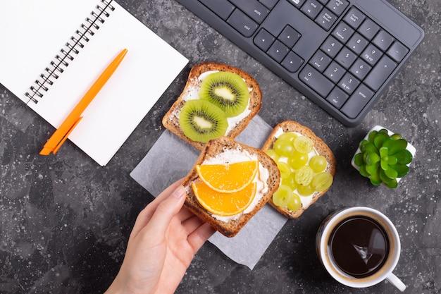 Donna che tiene a disposizione un panino con formaggio cremoso e spuntino sano arancio nel luogo di lavoro in ufficio