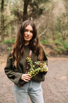 Donna che tiene alcuni fiori selvatici in natura