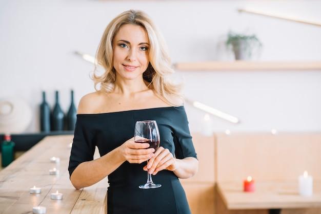 Donna che tiene bicchiere di vino e che affronta macchina fotografica