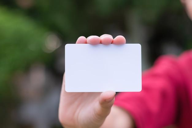 Donna che tiene biglietto da visita bianco su sfondo naturale bokeh