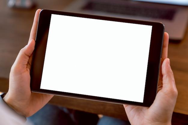 Donna che tiene compressa digitale dello schermo in bianco e del computer sull'ufficio della tavola. prendi lo schermo per mettere la pubblicità.
