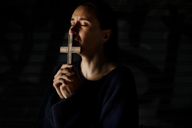 Donna che tiene croce che prega per la religione di dio