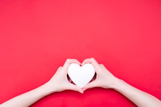 Donna che tiene cuore decorativo su rosso