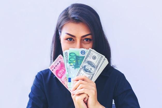 Donna che tiene dollari usd, yuan rmb, euro soldi scegliendo e pensando di affari