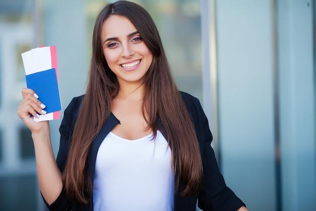 Donna che tiene due biglietti aerei nel passaporto all'estero vicino all'aeroporto