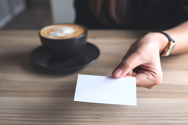 Donna che tiene e che dà un biglietto da visita vuoto a qualcuno con la tazza di caffè sul tavolo