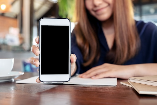 Donna che tiene e che mostra il telefono cellulare bianco con lo schermo nero in bianco