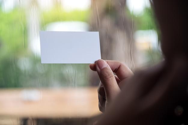 Donna che tiene e che mostra un biglietto da visita vuoto