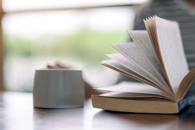 Donna che tiene e legge un libro mentre beve il caffè sul tavolo di legno