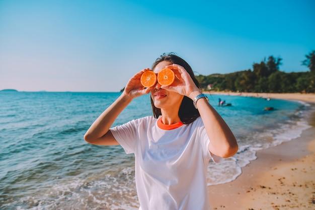 Donna che tiene fetta d'arancia in spiaggia mare sfondo