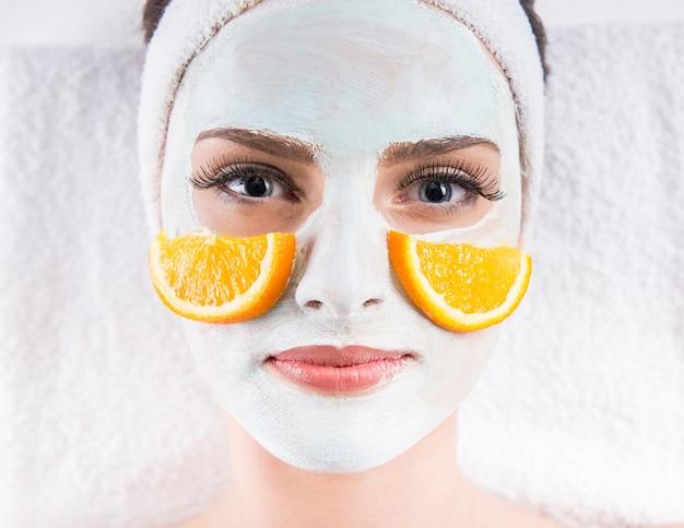 Donna che tiene fette d'arancia e maschera sul viso.
