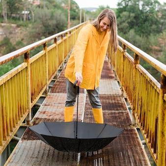 Donna che tiene giù un ombrello aperto
