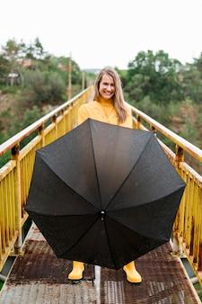 Donna che tiene giù un ombrello nero aperto