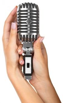 Donna che tiene grande microfono retrò per cantare